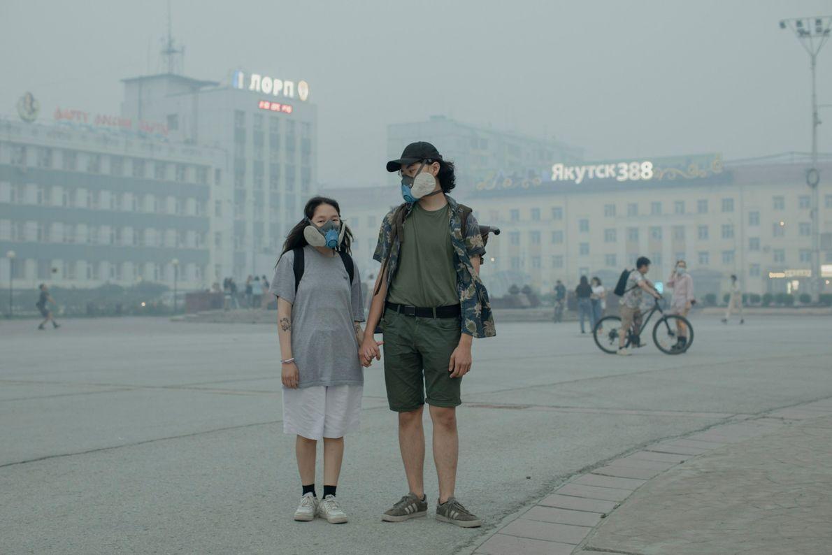 Elizabeth Yefimova, 18, und Ilya Alekseyev, 20, tragen Atemschutzmasken. Der Rauch der Waldbrände hängt tief über ...
