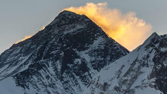 Hinter dem Gipfel des Mount Everest leuchtet das frühe Morgenlicht.