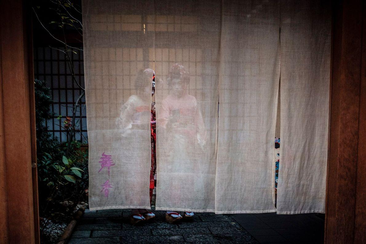 Zwei Maikos – erkennbar an ihren bunten, blumigen Stoffen und Accessoires – stehen am Eingang eines ...