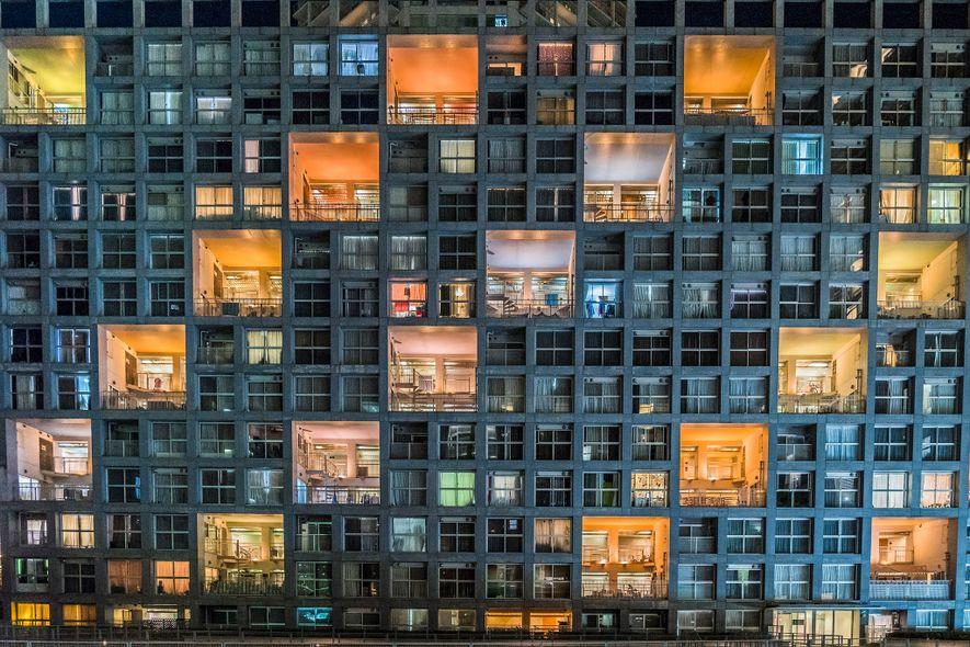 TOKIO, JAPAN Bunte Lichter bilden einen starken Kontrast zu den dunklen Fenstern eines Wohnkomplexes in der ...