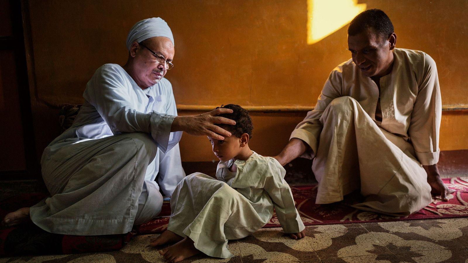 Mann betet über Jungen