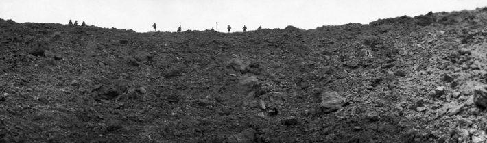 Alliierte Soldaten blicken in einen Explosionskrater