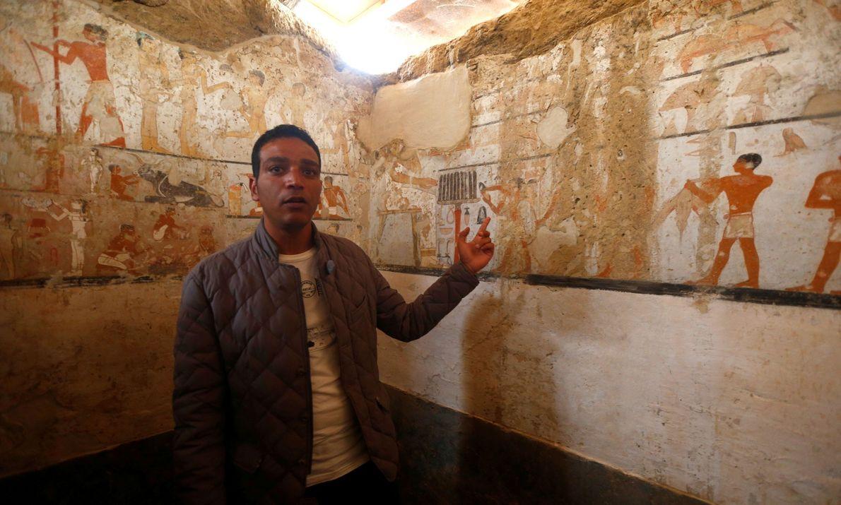Ein Führer des ägyptischen Antikenministeriums inspiziert eine Malerei, die im Grab der Priesterin Hetpet entdeckt wurde.