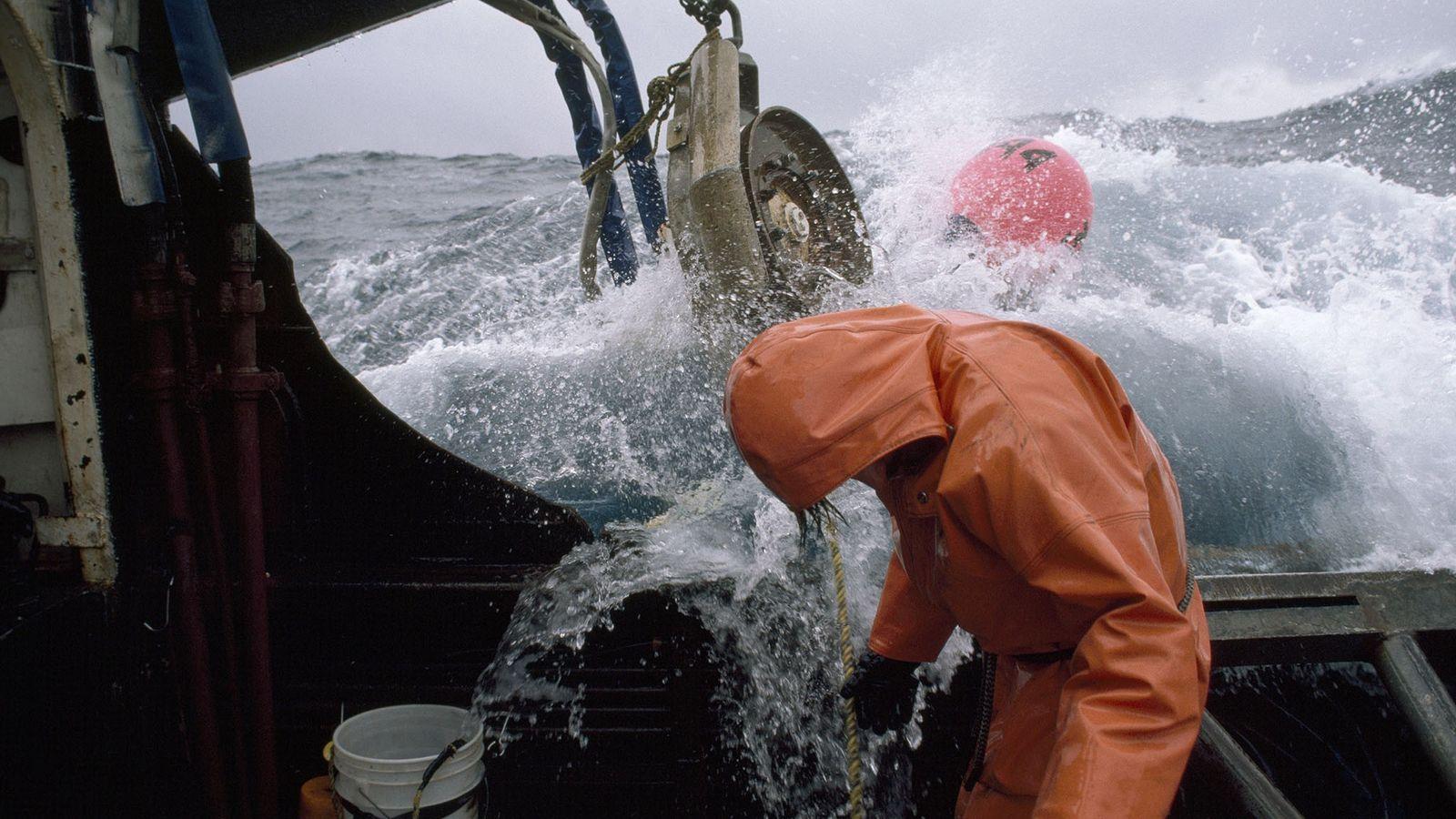 Ein Fischer überprüft auf hoher See seine Leinen.