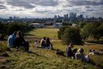 Menschen verbringen den Nachmittag im Greenwich Park und genießen den Blick auf die Skyline von London. ...