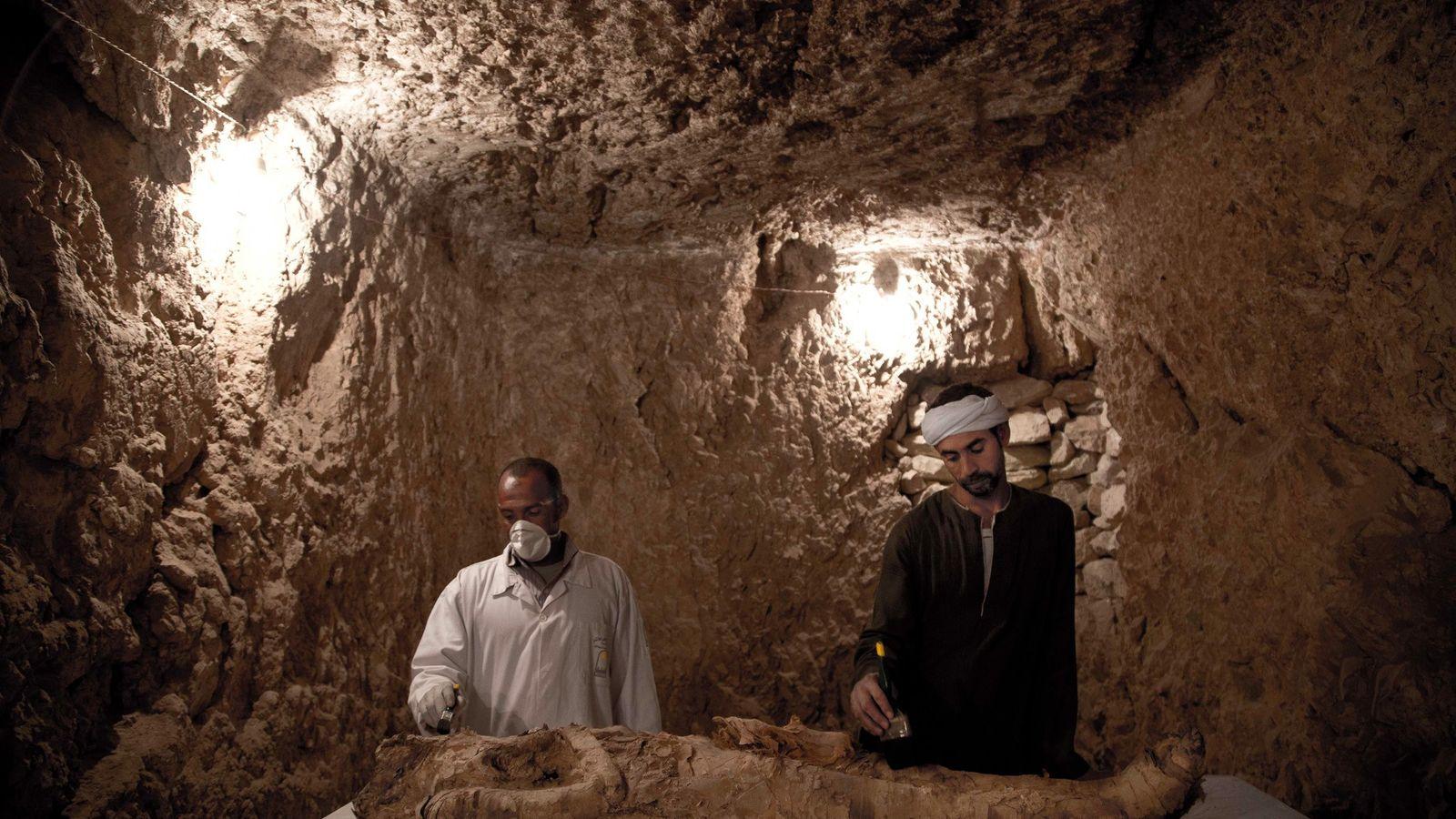 Arbeiter kümmern sich um eine Mumie in einem 3.500 Jahre alten Grab in Ägypten.