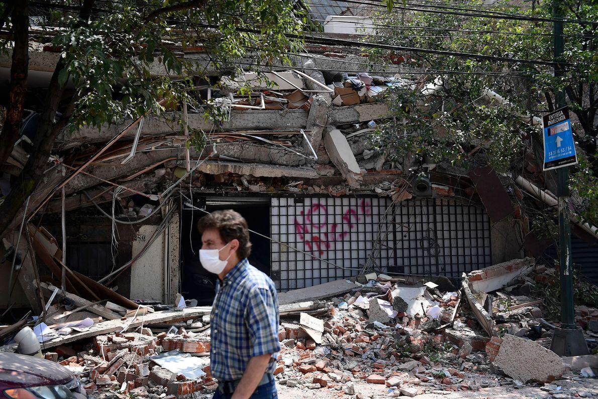 Ein Mann läuft an einem Gebäude vorbei, das durch das Erdbeben eingestürzt ist. Viele Menschen erinnert ...