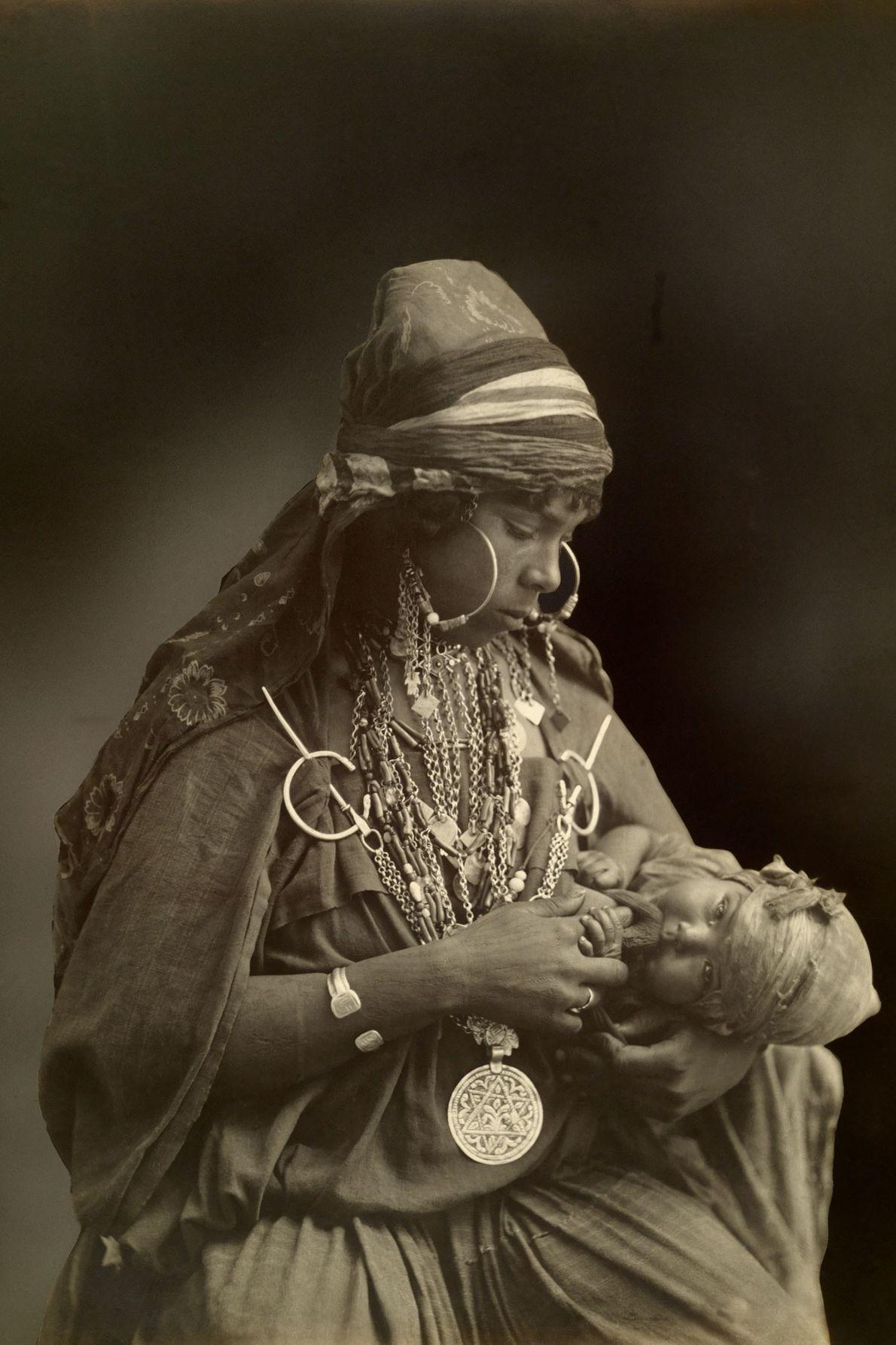 Eine Beduinenmutter mit prächtigem Schmuck blickt auf ihr Kind hinab. Die Aufnahme entstand Anfang des 20. ...