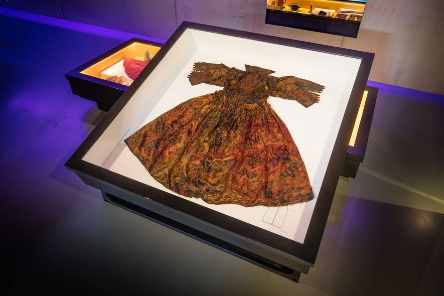 Das Kleid wurde aus Seide und Damast gefertigt. In den Stoff wurde ein florales Motiv eingewebt. …