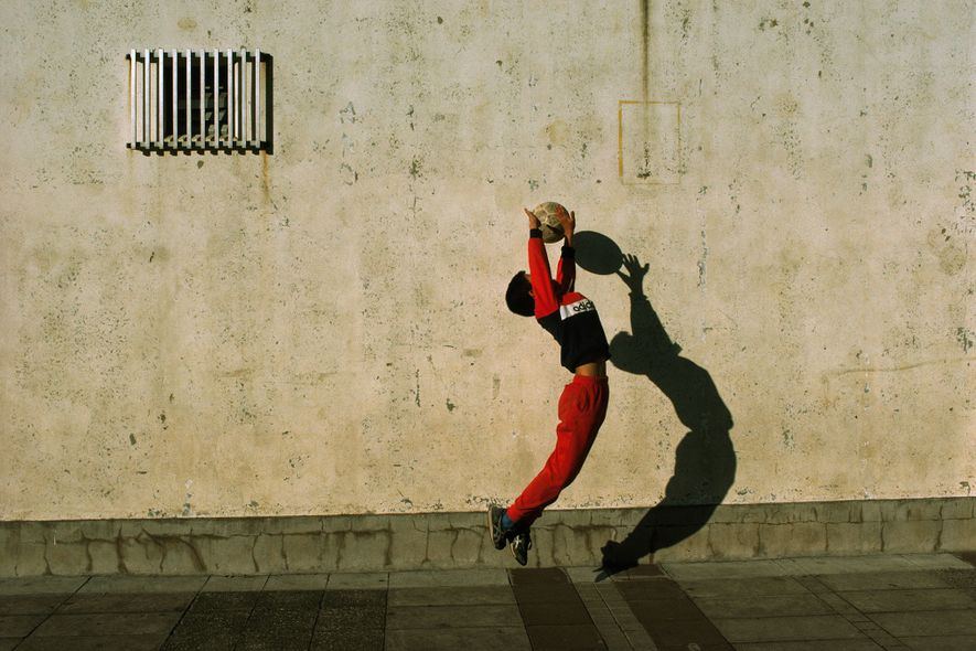 Im japanischen Tokio spielen Schüler auf dem Schulhof eine Runde Fußball. Der Torwart springt in die ...