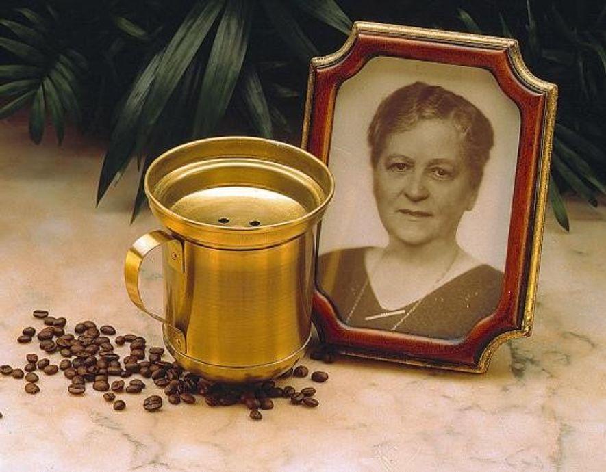 Ein Foto von Melitta Bentz neben einem Messingbecher und Kaffeebohnen.