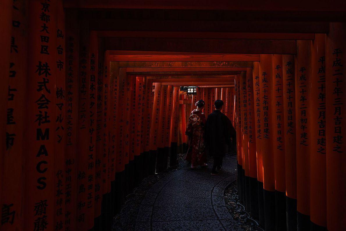 Ein Paar in traditioneller japanischer Kleidung schreitet durch einen der berühmten Torii-Wege des Shinto-Schreins Fushimi Inari-Taisha. ...