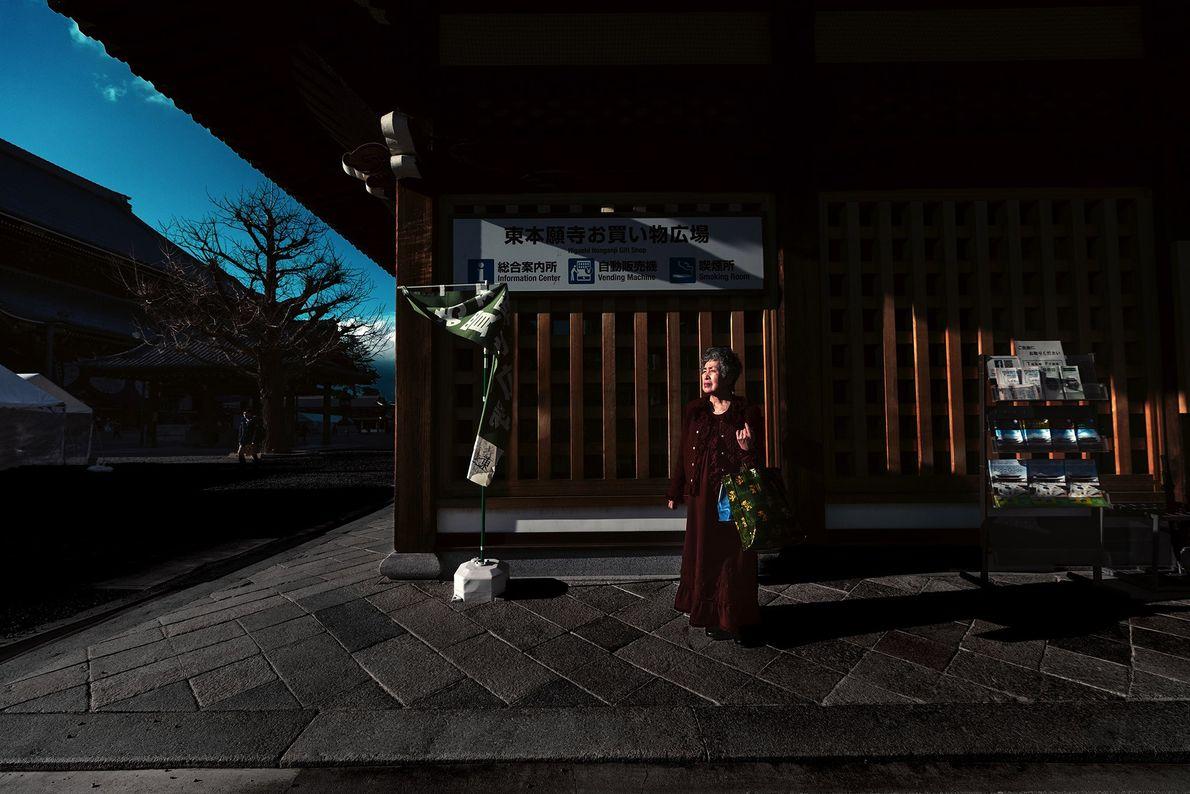 Eine Frau steht vor einem Gebäude auf dem Gelände des großes Tempels Higashi Hongan-ji. Der architektonisch ...