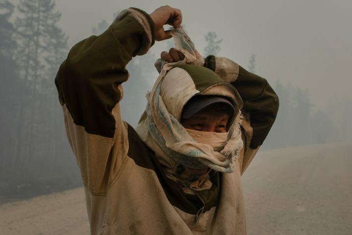 Ein freiwilliger Feuerwehrmann bedeckt sein Gesicht, bevor er bei der Eindämmung eines Waldbrands in der Nähe ...