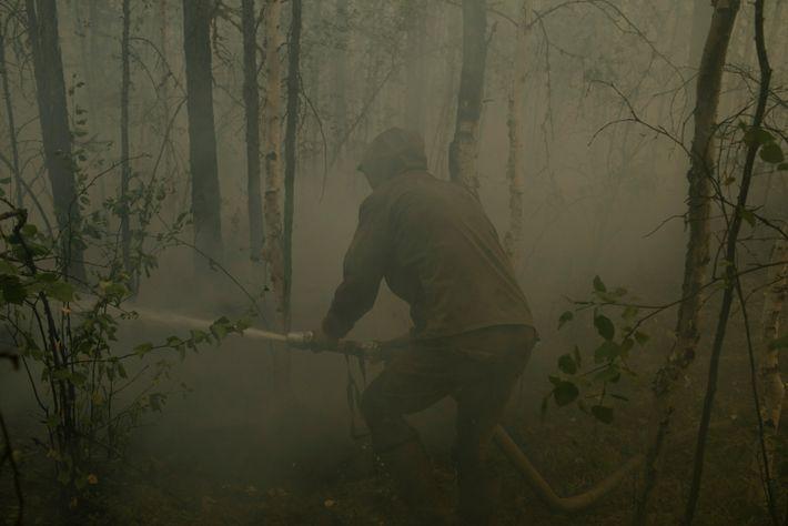 Der freiwillige Feuerwehrmann Kim Konstantinov, 36, kämpft in der Nähe von Kyuyorelyakh gegen einen Waldbrand an.