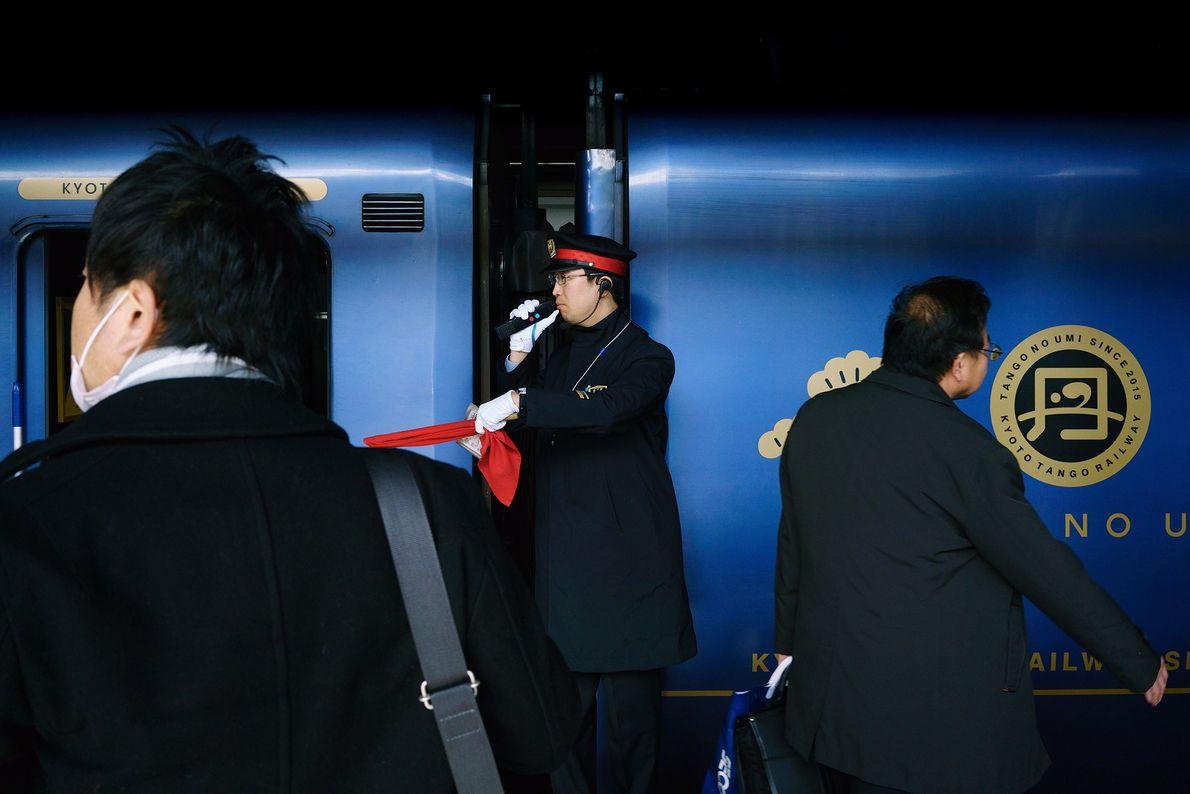 Ein Bahnhofsmitarbeiter mit weißen Handschuhen vermeldet die Abfahrt des Zuges. Die Mitarbeiter benutzen ein spezielles System ...