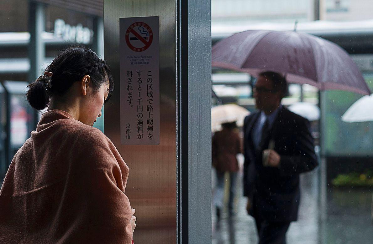 Ein Fahrgast sucht an einer Haltestelle Schutz vor dem Regen. Wie auch in Tokio dauert die ...