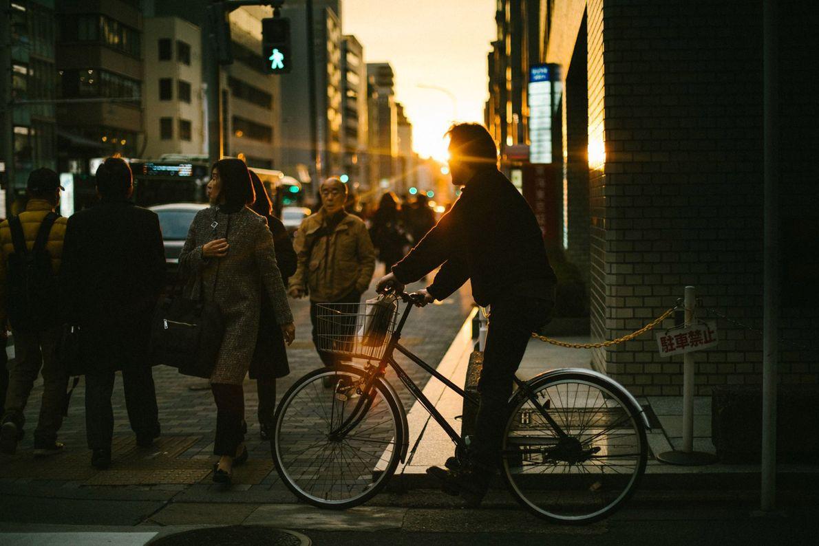 Die untergehende Sonne wirft ihr goldenes Licht auf eine geschäftige Straße in Kyoto.