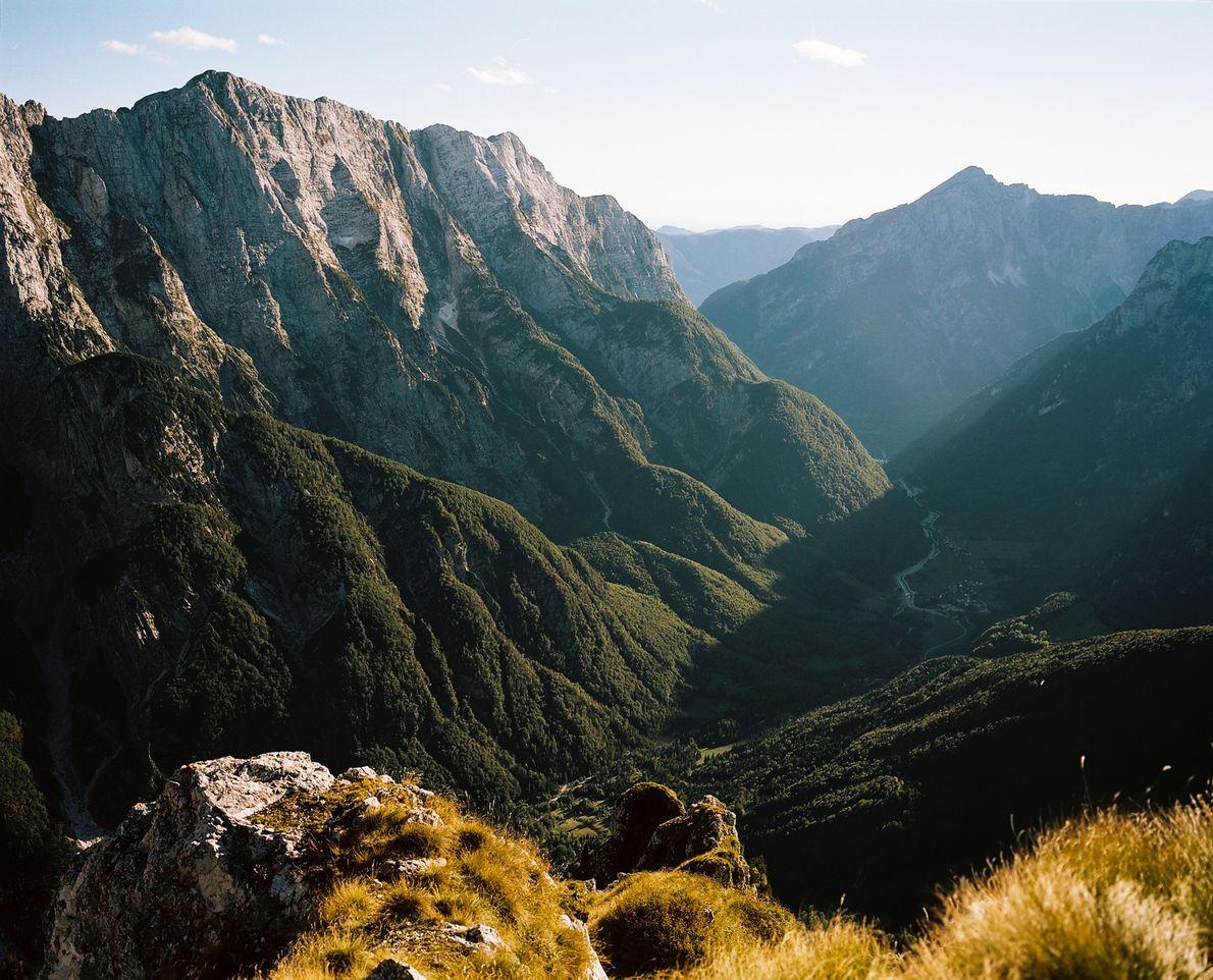 Sonnenlicht bringt das Grün im Tal unterhalb des Mangart zum leuchten, das versteckt in den Julischen ...