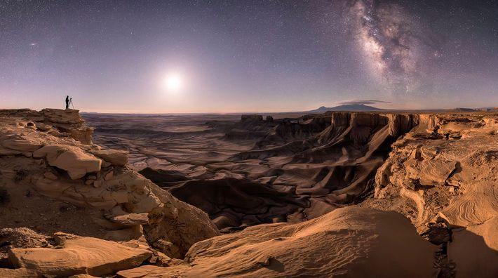 In Moab im US-Bundesstaat Utah steht ein Fotograf auf einem Felsen. Am Nachthimmel sind der Mond, ...