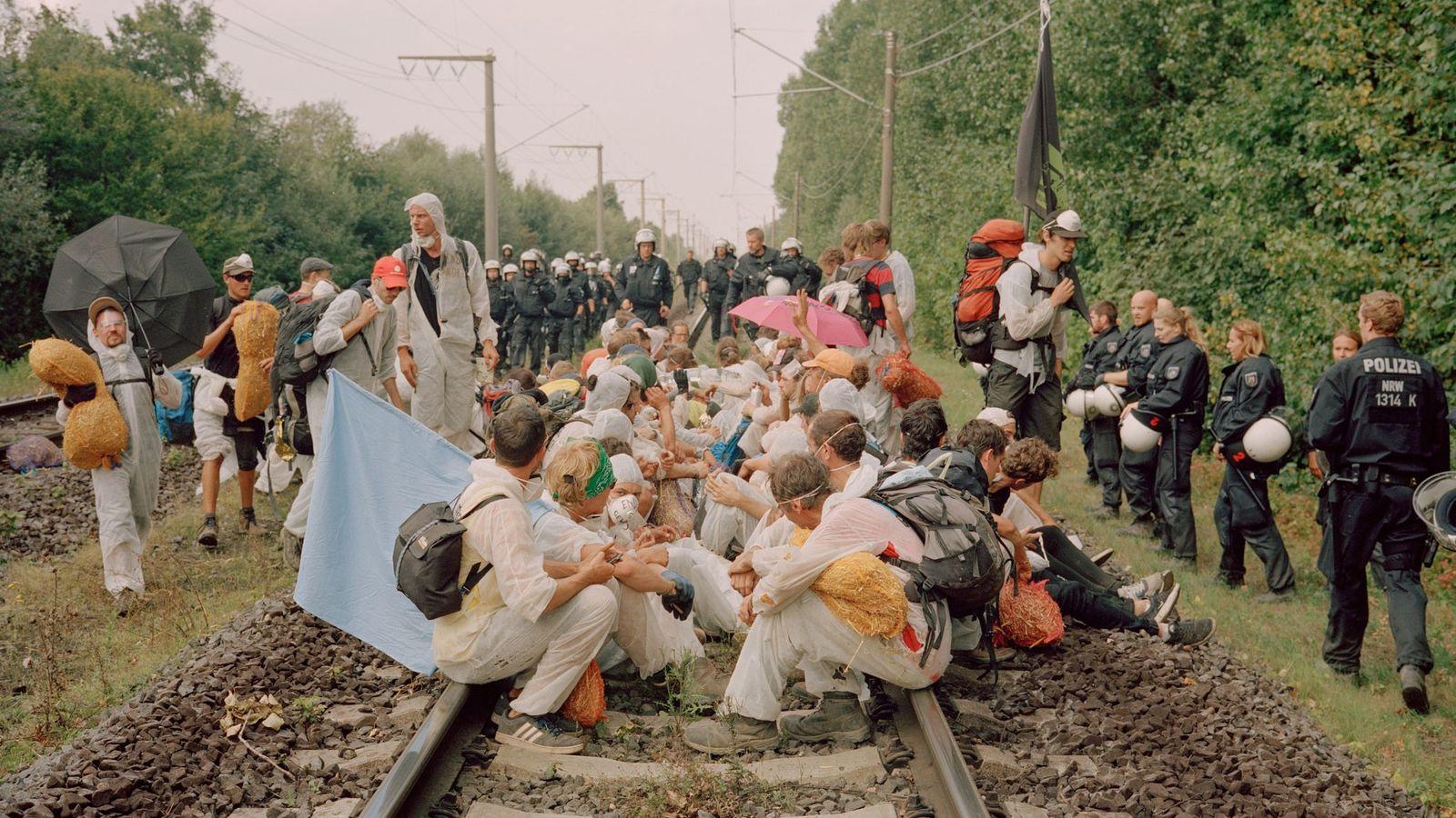 Demonstranten sitzen auf den Schienen für die Kohlegüterzüge, als Polizisten dazustoßen und sie umringen.
