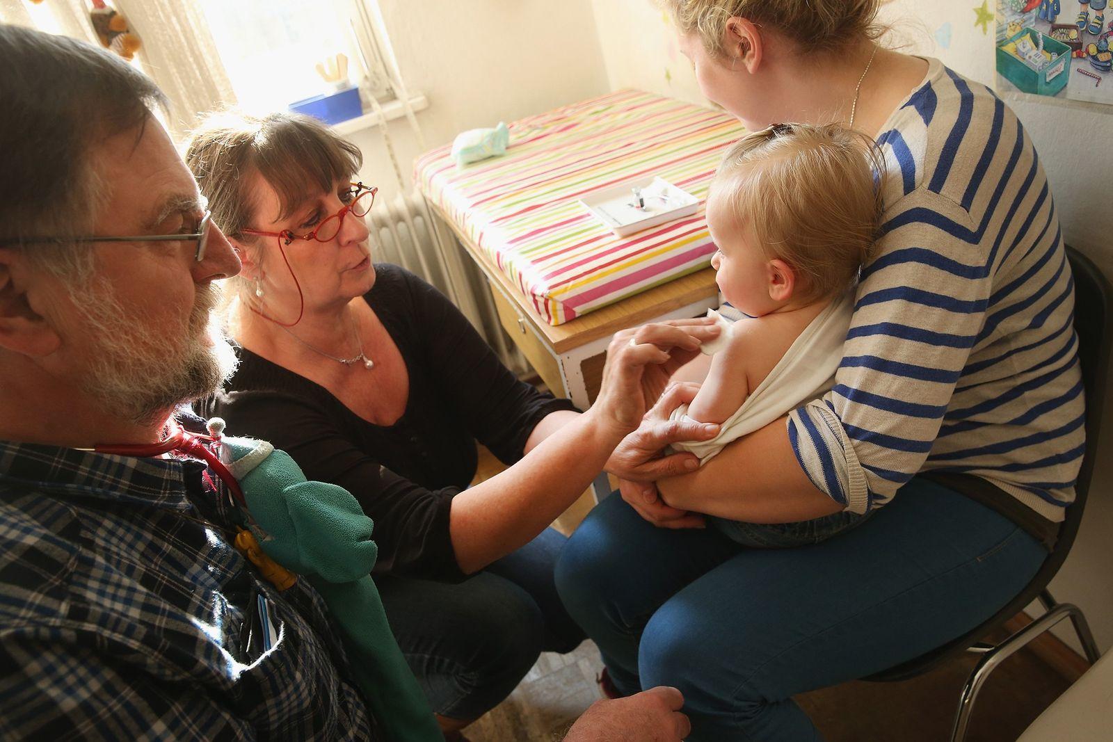 Eine Arzthelferin bereitet die elf Monate alte Tijana 2015 in Berlin auf eine Impfung gegen Masern, ...