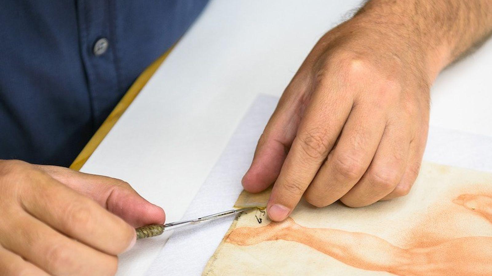 Nachdem das Hydrogel den Kleber gelöst hat, entfernt ein Restaurator das Klebeband.