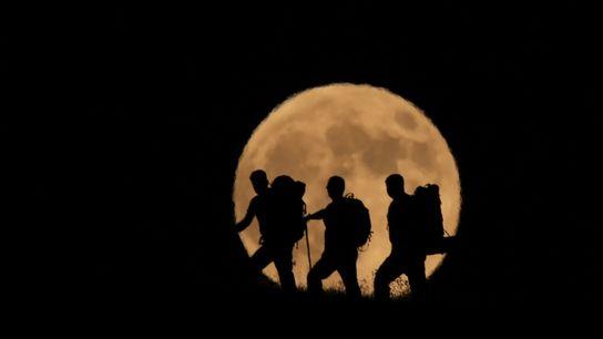 Der Vollmond geht am 27. Juli hinter drei Bergsteigern auf dem Artos in der Türkei auf. ...