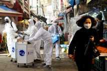 Eine Frau mit einer Maske läuft am 26. Februar 2020 über einen Markt in Seoul, Südkorea, ...