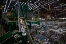 Ein Förderband leitet gemischten Plastikmüll in eine optische Sortieranlage.