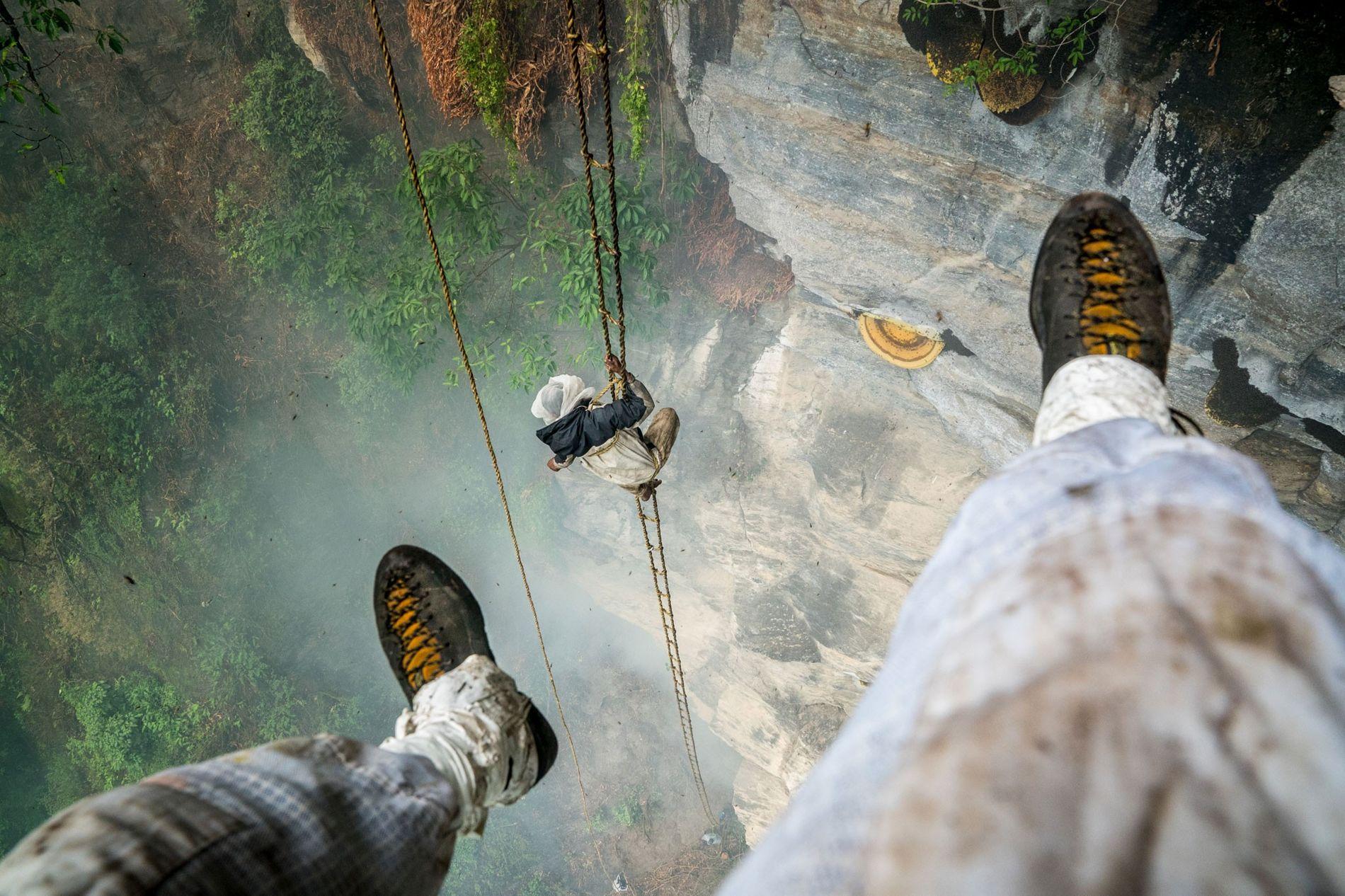 Renan Ozturk schoss dieses Foto, als er in der Luft an einem Seil hing. Der letzte Honigjäger Nepals, Mauli Dhan, erklimmt im Hintergrund die Felswand auf seiner handgemachten Strickleiter. Ozturk hat seine Fußgelenke mit Tape abgedichtet, damit keine Bienen unter seine Kleidung kriechen.