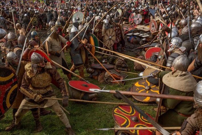 Mit Schwertern und Speeren bewaffnete Wikinger- und Slawen-Reenactors begegnen sich im gestellten Kampf auf einem Festival ...