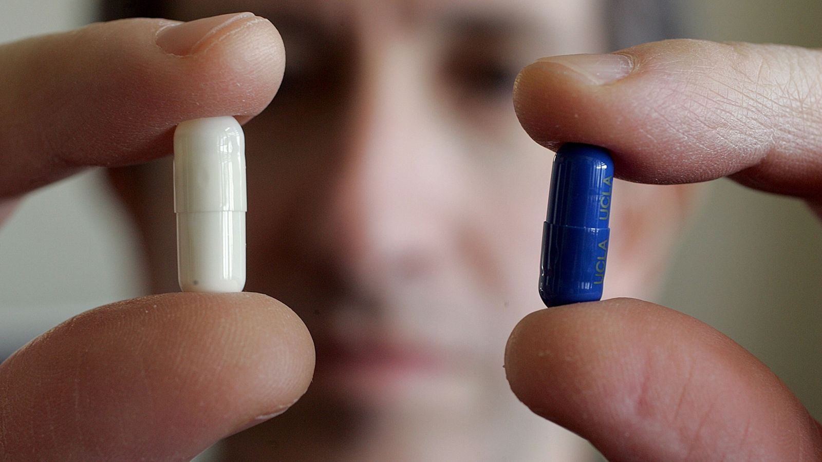 Der Psychiater Andrew Leuchter hält zwei Pillen in seinen Händen – bei der einen handelt es ...