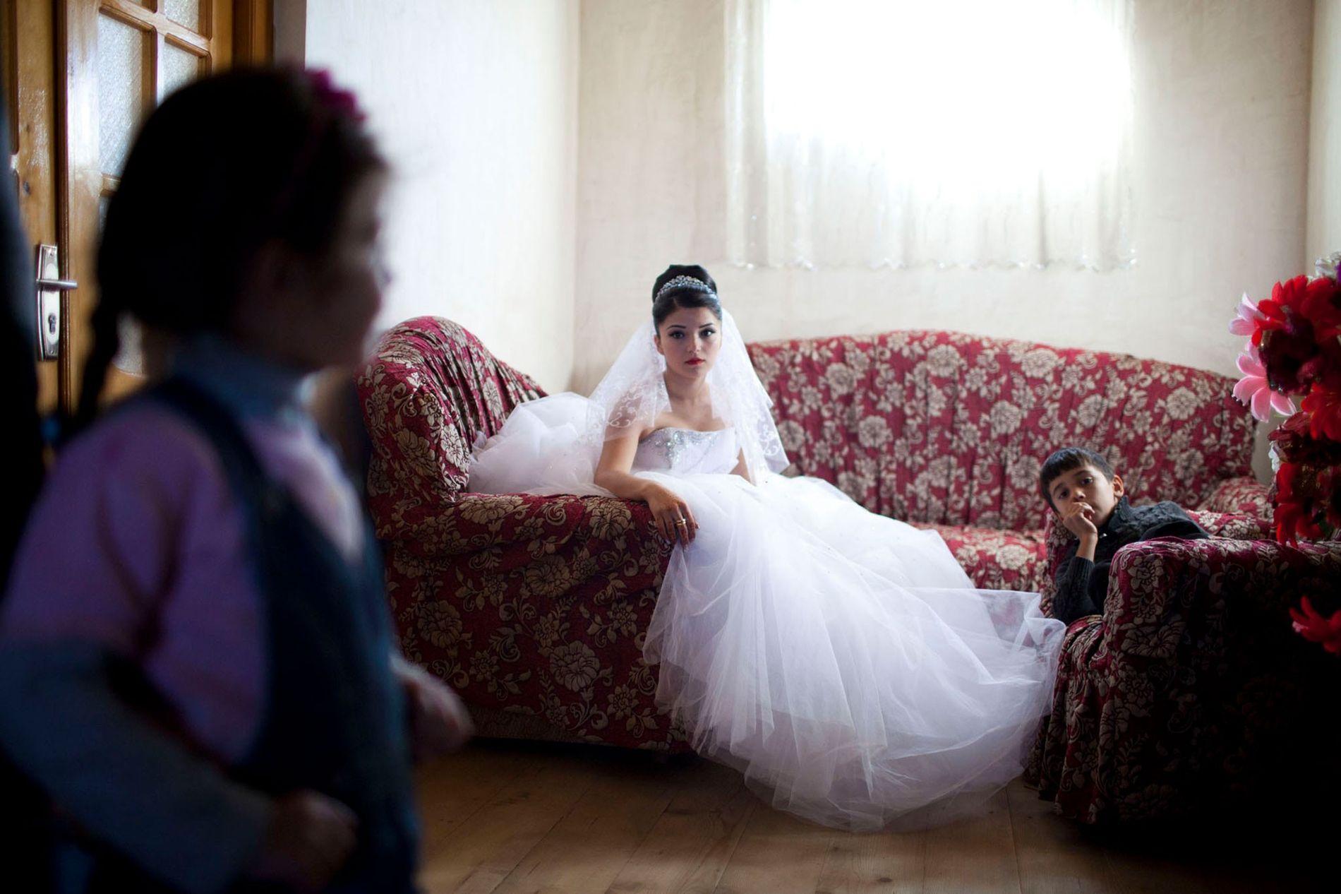 Foto einer jugendlichen Braut auf einem geblümten Sofa