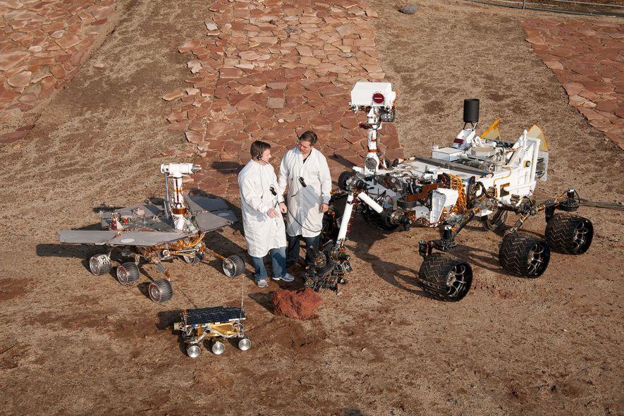 Zwei NASA-Techniker posieren mit Mars-Rovern aus drei Generationen, die im Jet Propulsion Laboratory in Pasadena, Kalifornien ...