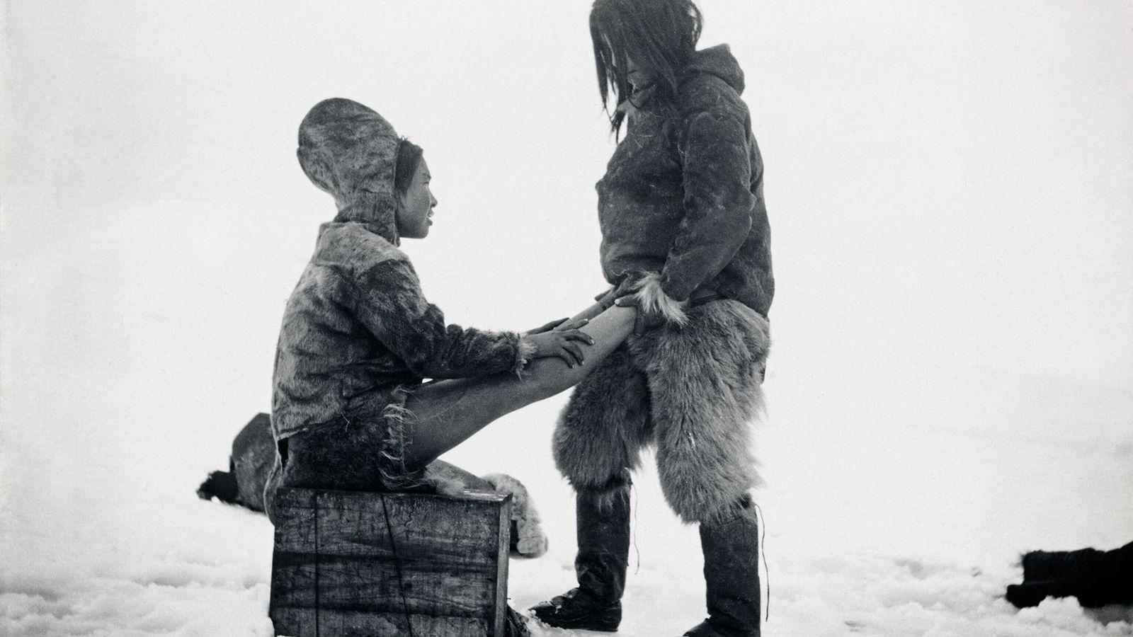 Ein Inuk wärmt in Peterrahwik, Grönland, die Füße seiner Ehefrau.