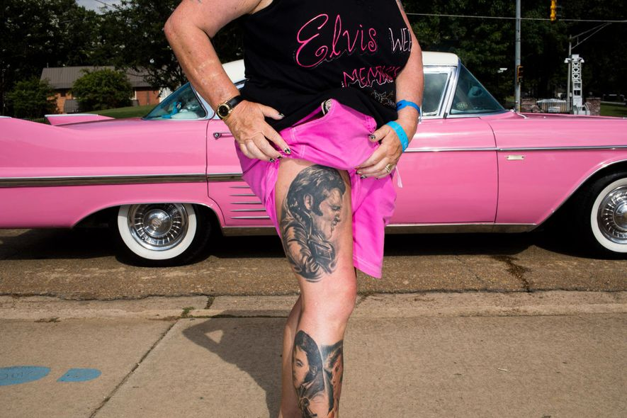 Sharon O'Brien aus Großbritannien zeigt ihre sechs Elvis-Tattoos. Hinter ihr steht ein rosa 1958er Cadillac auf dem Elvis Presley Boulevard. Sie besucht Graceland zum siebten Mal.