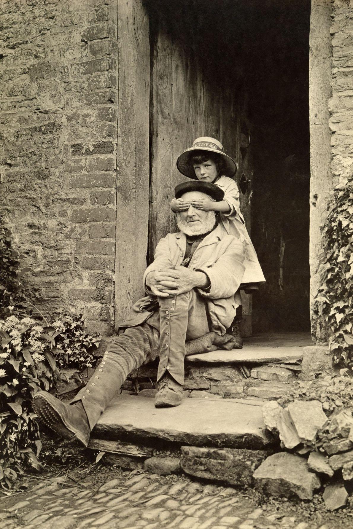 Ein Mädchen steht hinter ihrem Großvater, der auf der Eingangstreppe vor einem Haus in England sitzt, ...