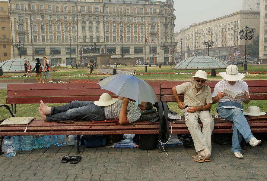 Auf diesem Foto vom 9. August 2010 ruhen sich Menschen auf dem Manezhnaya-Platz vor dem Kreml ...