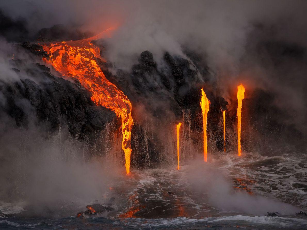 Ein Lavafluss bricht aus der Seite des Vulkans und fließt ins Meer. Die Aufnahme entstand von ...