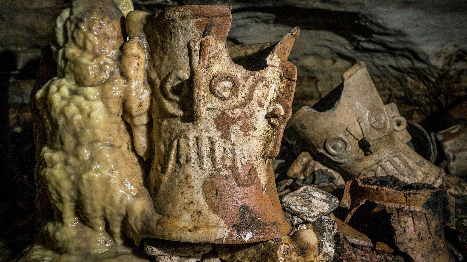 Im Laufe der Jahrhunderte haben sich Stalagmiten rund um die rituellen Objekte wie dieses Räuchergefäß gebildet, ...
