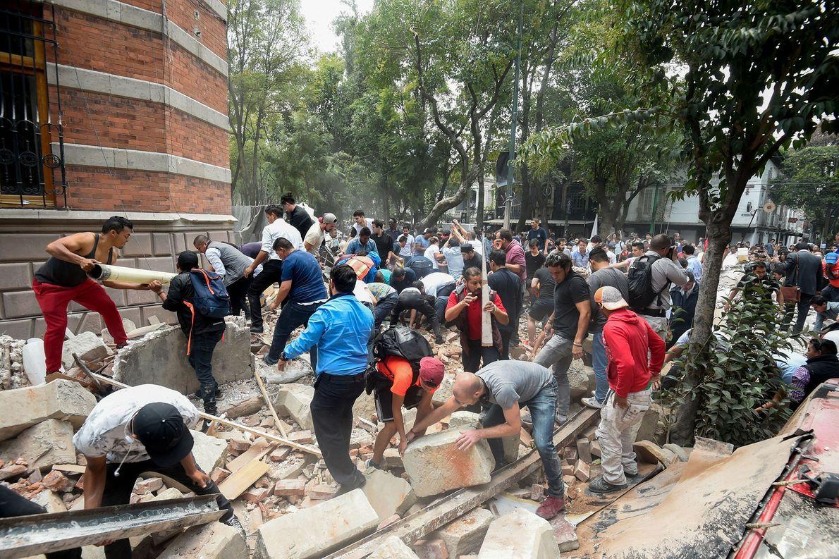Menschen beseitigen die Trümmer eines Gebäudes, das durch das Erdbeben eingestürzt ist.