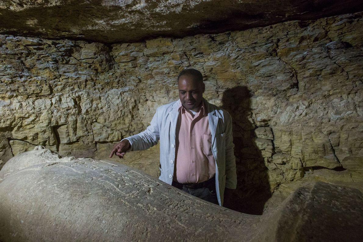 Ein ägyptischer Mitarbeiter der Ausgrabung präsentiert einen Sarkophag, der in einer großen Totenstadt gefunden wurde.