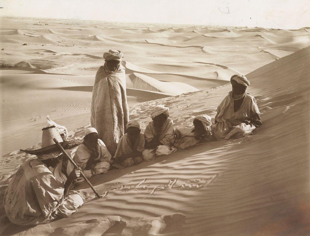 Schüler in einer Wüstenschule in der Sahara folgen aufmerksam einer Lektion, die ihr Lehrer in den ...