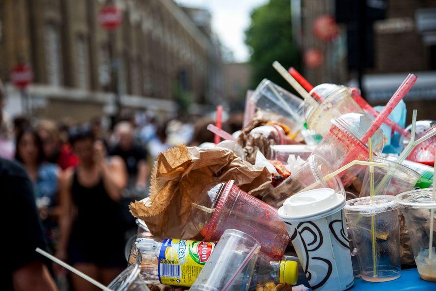 Müll quillt aus den Mülleimern auf dem Brick Lane Market in Londons East End. Plastikstrohhalme gucken ...