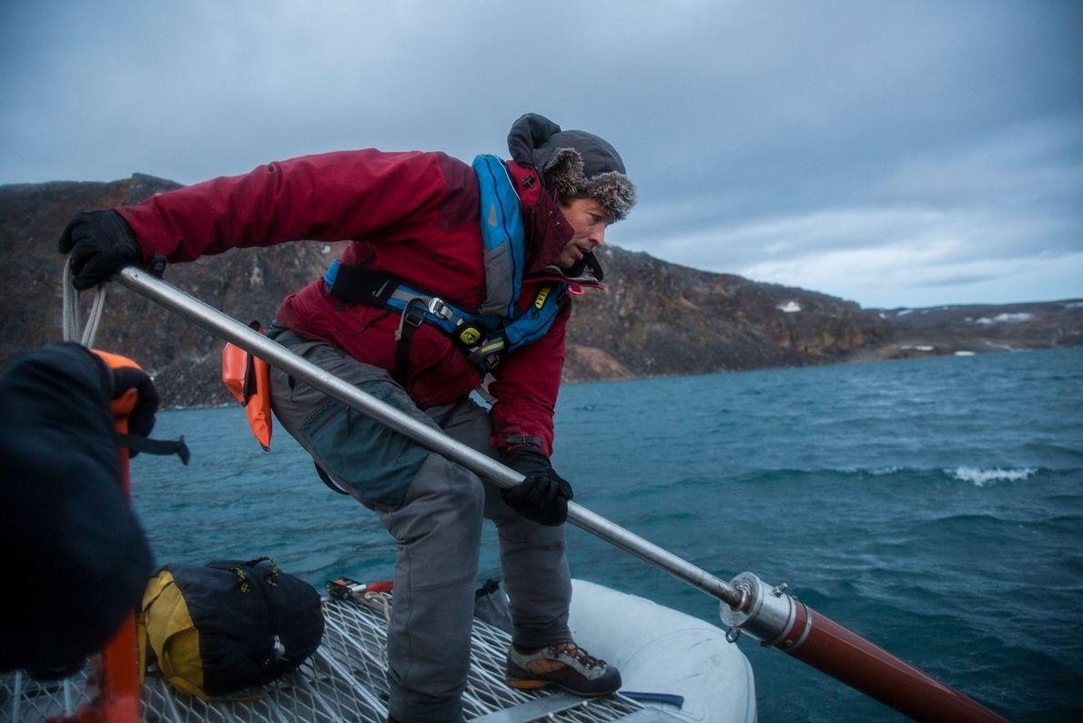 Jostein Bakke von der Universität Bergen hält eine Apparatur zur Kernbohrung ins Wasser des Ringgåsvatnet-Sees auf ...