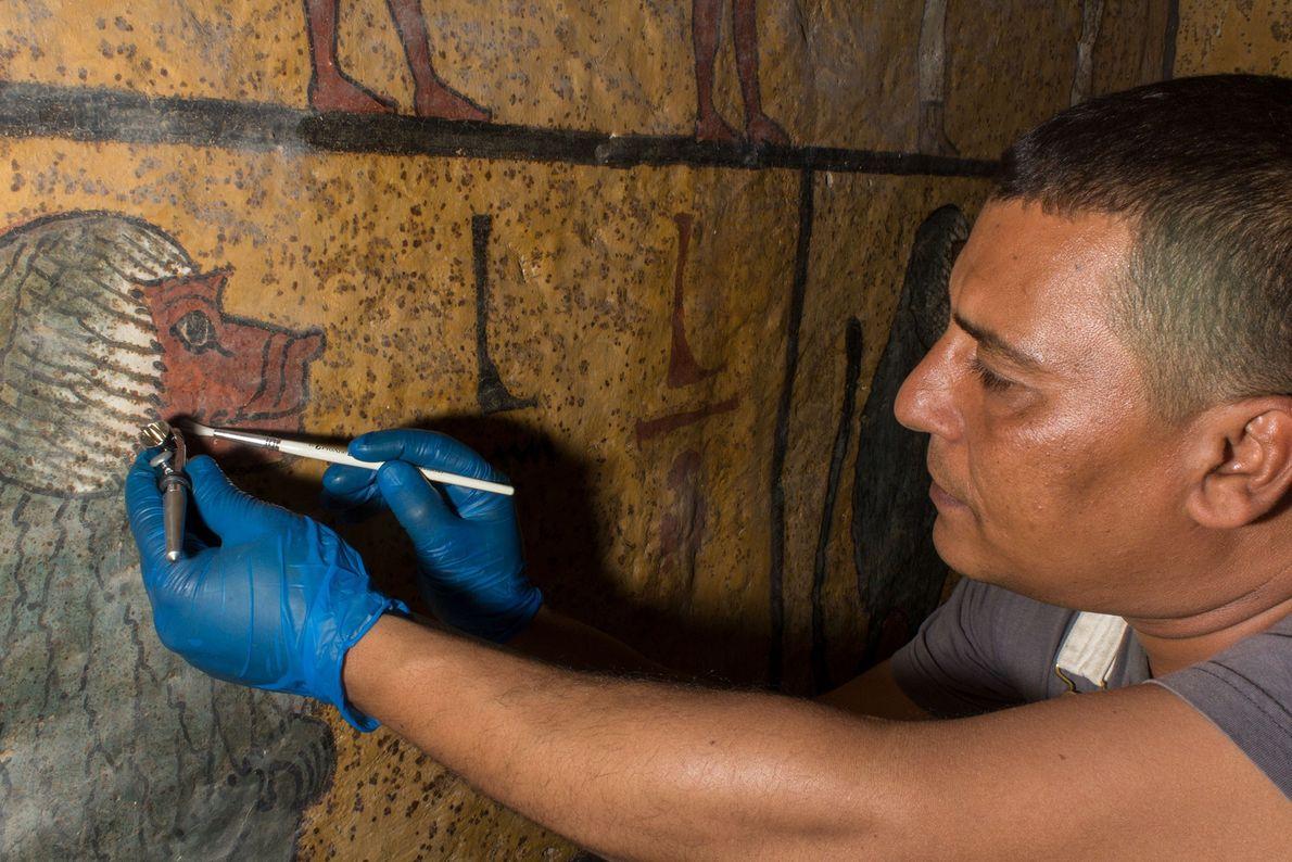 Vorsichtig entfernt ein Restaurator mit einem Pinsel klebrigen Staub von den bemalten Wänden in Tutanchamuns Grab. ...