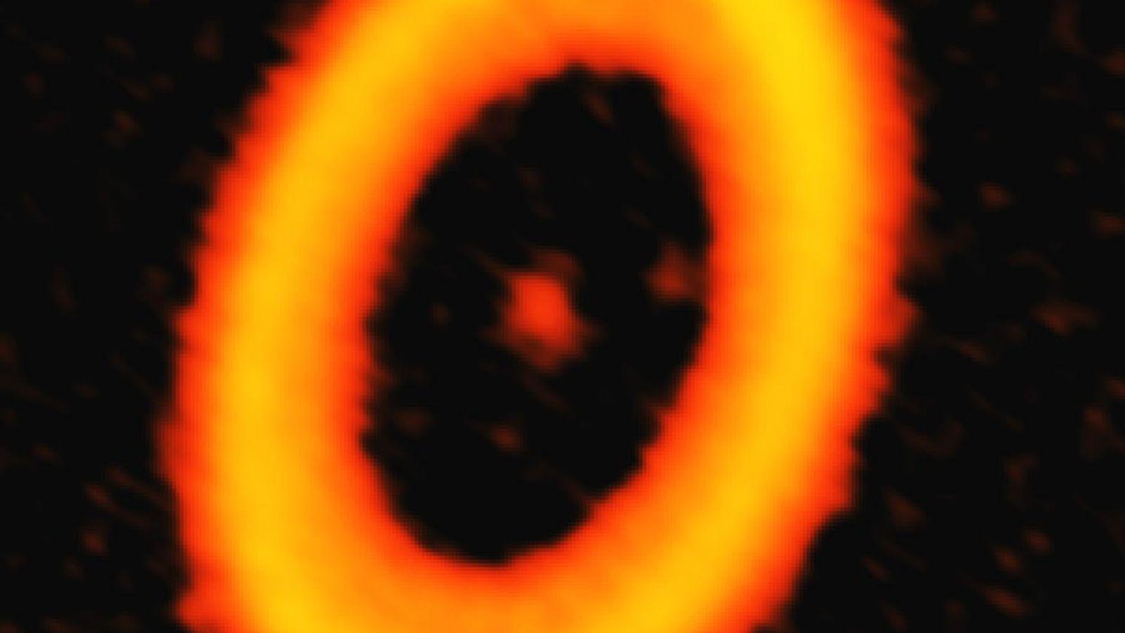 Dieses ALMA-Bild einer Staubwolke im Sternsystems PDS 70 lässt zwei blasse Flecke in der protoplanetaren Scheibe ...