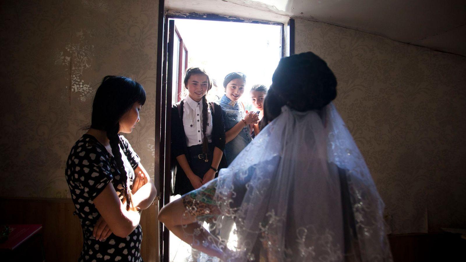 Foto von jungen Mädchen, die das Hochzeitskleid ihrer Freundin bewundern