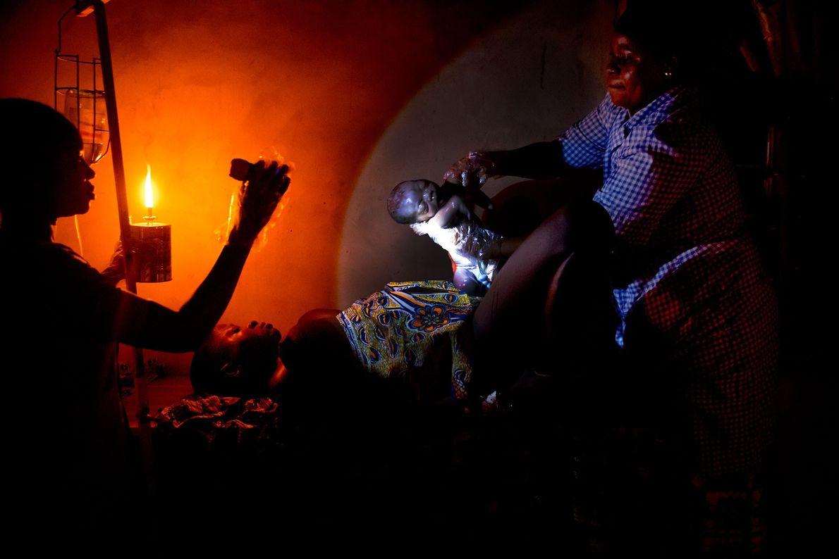 Die Hebamme Raïssa Godjo hilft bei der Geburt eines Babys im Dorf Attankpe. Die einzigen Lichtquellen ...